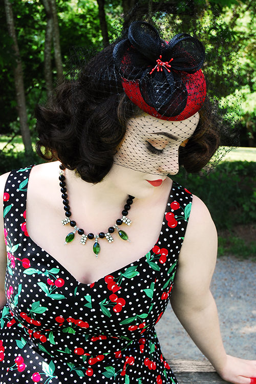 Vintage style model Kristen Meyn wearing a Cherry Velvet polka Dot dress with a hat by Maria Curcic